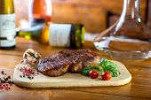 stock photo of graphene  - A big pork steak with spices tomatoes and bottles of wine on the background - JPG