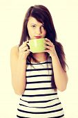 Young woman drinking something hot from big mug