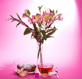 Appetizing cupcake on a dish, tea and alstroemeria