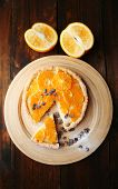 Homemade orange tart with coffee grains on wooden background