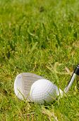 Golf ball on a tee with pitching wedge