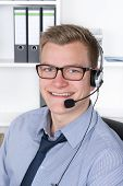 Young Smiling Man With Headset In The Office