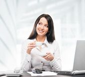 Young and attractive business woman drinking morning coffee in office