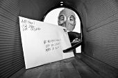 Постер, плакат: A unidentifiable person in a Gas Mask retrieves or sends mail from their mail box with an extension