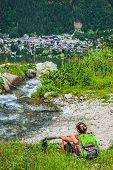 Woman sitting on a background of mountains and running down the creek, France, Europe