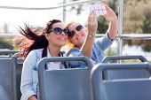 two tourists taking a selfie with smart phone on an open top bus