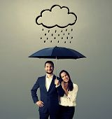 smiley young couple with black umbrella standing under drawing storm cloud. photo over grey background