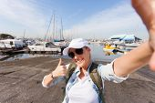 happy tourist taking self portrait with thumb up