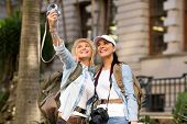 happy tourists taking self portrait together in city