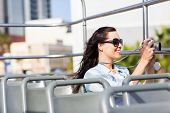 female traveller taking video of the city using digital camera from an open top bus
