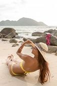 Thai girl with straw hat laying on the beach