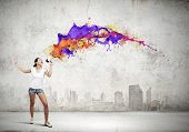 Young woman in casual speaking in megaphone with colorful splashes flying out