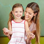 Happy mother with smiling daughter in front of a chalkboard