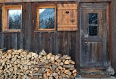 stock photo of chalet  - firewood stacked in front of a wooden chalet - JPG