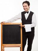 Professional waiter showing an empty blackboard