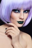Close-up portrait of young beautiful woman with colorful fancy make-up and violet wig