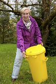 Woman With Dustbin In Garden