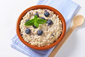 oatmeal with fresh blueberries, served in the bowl with fabric linen and wooden spoon