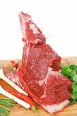 raw meat : fresh beef pork big rib piece with garlic and green stuff on wood isolated over white bac
