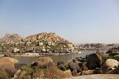 Hill with amazing stones and river at Hampi temple complex in India