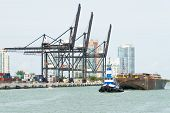 MIAMI,USA - MAY 27,2014 : Tugboat pulling a barge in the Port of Miami with containers and cranes on