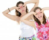 Portrait of a two teen girls have fun and make faces looking and searching something, isolated on wh