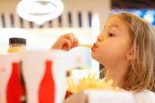 Little girl eating fast food