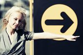 Young fashion blond woman pointing a direction