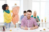 startup, education, fashion and office concept - smiling male drawing sketches and female adjusting dress on mannequin in office