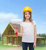 construction and people concept - smiling little girl in protective helmet with paint roller