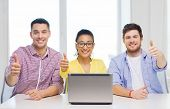 education, technology, business, startup and office concept - three smiling colleagues with laptop i