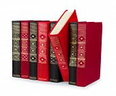Stack Of Vintage Red And Black Book With Gold Ornament On A White Background