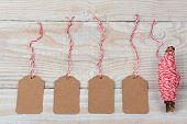 High angle shot of four blank gift tags and red and white string wrapped around a twig laying on a rustic whitewashed wooden table. Horizontal format.