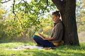 Distance education. Young woman sitting near from tree and working with tablet.
