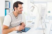 Casual man working at desk with computer and digitizer in his office