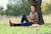 picture of knitwear  - Young woman have rest with book under the tree during picnic - JPG
