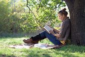 Young Woman Reading Book Under The Tree During Picnic In Evening Sunlight