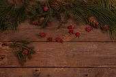 Still-life with fur-tree both pine branches and cones and decorative red apples on a wooden table