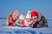 Happy couple and two kids in winterwear lying in snow