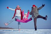 Joyful family of father, mother and daughter in winterwear