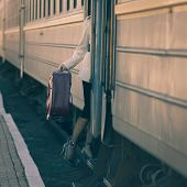 Fashionable Woman Entering Into Train Car. Holding A Suitcase