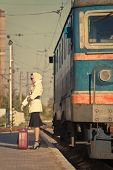 Woman In Sunglasses Waiting Train On Railroad Station. The Autumn Cold Weather. Beige Coat. Retro Su