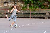 Pretty teenage girl playing football