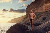 very muscular handsome guy standing on rocky beach, on sky background. outdoor