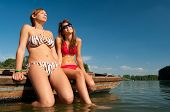 Cute teenage girls sunbathing on the boat on sunny summer day