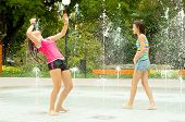 Teenage girls having fun in the towns water fountain on hot summer day