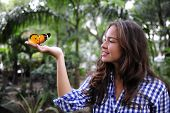 Butterfly Sitting On The Hand Of A Young Woman In The Forest
