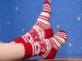 Feet With Christmas Socks On The Desk At Home