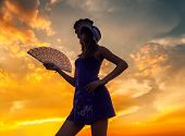 Beautiful Girl With Fan And Hat Outdoor