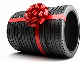 image of gift wrapped  - Gift set of tires wrapped ribbon and bow isolated - JPG